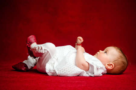 Adorable seven months old newborn cuttie, sitting on her back over a red background holding his feet and hands in the air photo