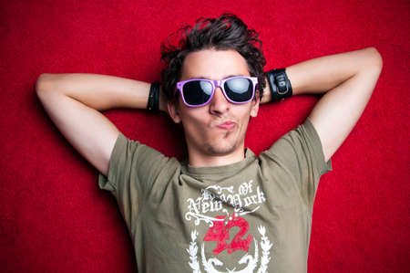 Young model making strange faces on red background, wearing purple sunglasses. isolated photo