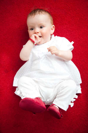 sandles: Little adorable newborn, lying on his back with red little sandles and white, cute dress. isolated on red background