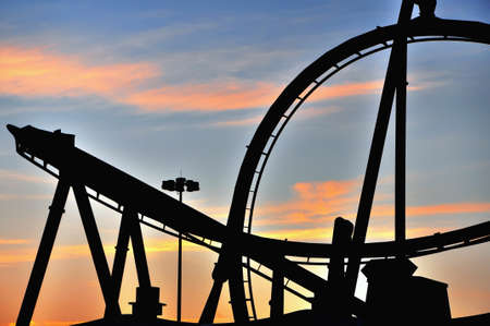 boardwalk: Sunset silhouette of a roller coaster in a theme amusement park Stock Photo