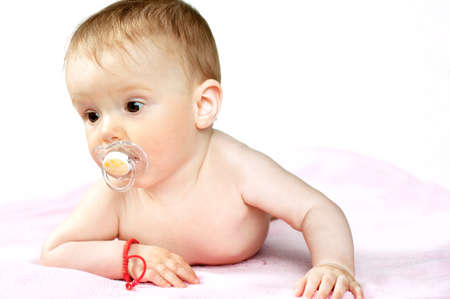 baby with soother: Seven Months old newborn, with a pacifier in her mouth, isolated on pink blanket and white background Stock Photo