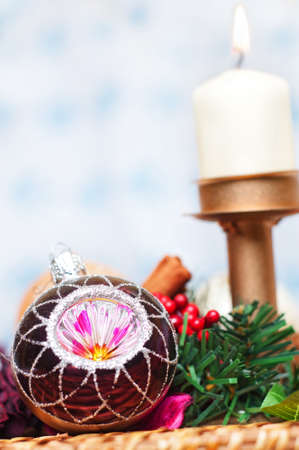 Christmas Ball with pine tree, berries and candle over a white and blue background photo