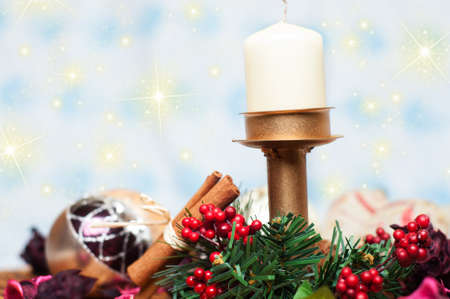 Christmas Candle with cinnamon and christmas tree balls over shiny background photo