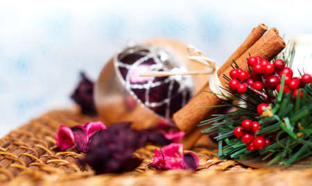 Christmas decoration with balls, flower petals and cinnamon over snowy background photo