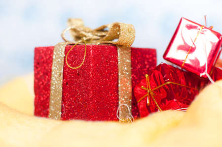 Red little shiny presents on a fluffy yellow surface isolated over white and blue background photo