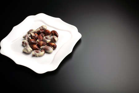 Little pieces of swiss chocolate seashells on white fancy plate, isolated on black background, with copy-space Stock Photo - 11963277