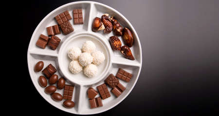 Lots of small chocolate flavours on white plate isolated on dark background Stock Photo - 12002538