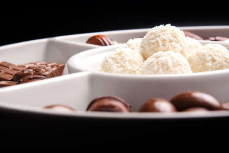 White coconut  and brown chocolate balls on plate, isolated on black background  photo