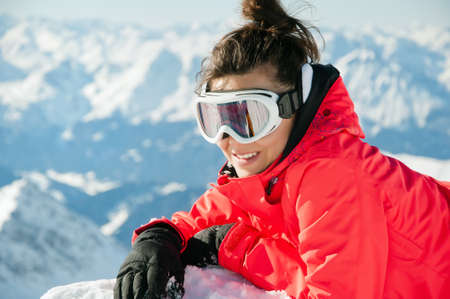 Woman wearing ski equipment and goggles resting on the top of a high mountain with alps background Stock Photo - 12819670
