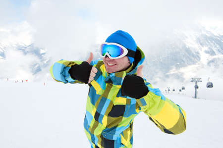 Man wearing ski equipment, smiling on slope with mountains background Stock Photo