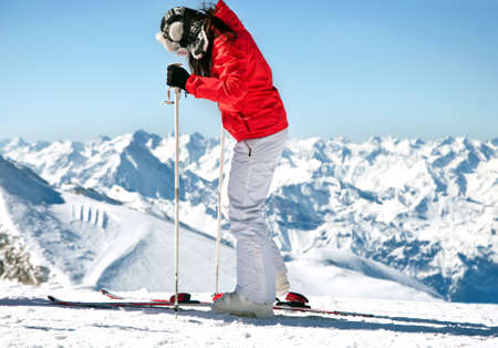 Female skier on ski slope in european alps with mountain background photo