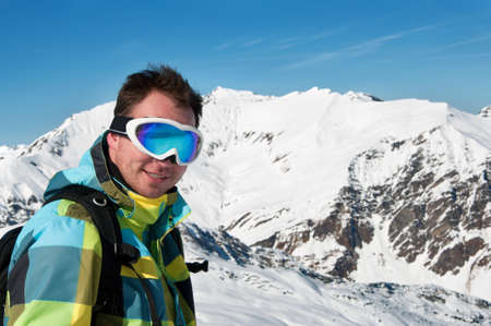 Male wearing goggles and ski jacket smiling on top of high european alps mountains photo