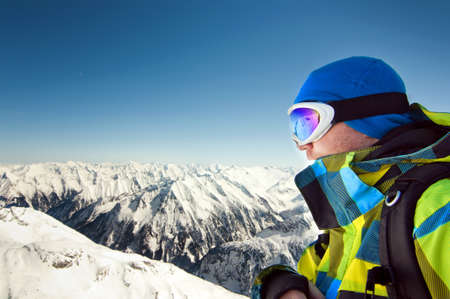 Male wearing ski equipment stands on top of high European Alps, ready for the winter season photo