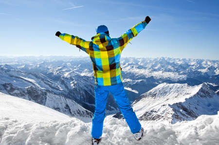 snow break: Male wearing ski equipment being excited about climbing on top of European Alps on a sunny winter day
