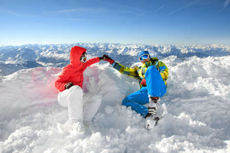 Happy lovers holding hands on the top of a ski slope with mountains background photo