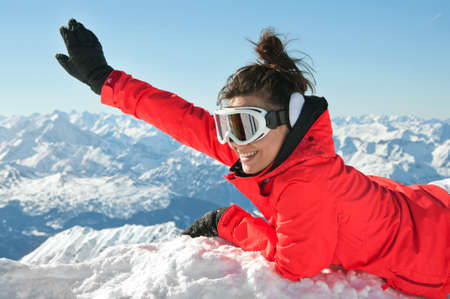 Girl waving from top of european Alps with a huge smile on her face photo