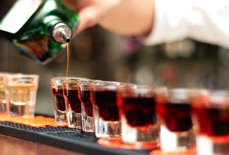 distilled: Bartender versa bevanda alcolica in bicchierini sulla barra