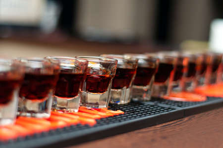 shooter drink: Red, strong alcoholic drink in small glasses on bar waiting to be served