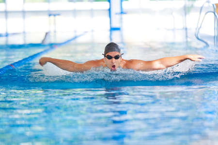 Man breathing while swimming  butterfly strokes in competition wearing swimming goggles and cap