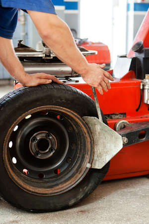 Auto mechanic manually changing the tyres on a classic rim Stock Photo - 15449848