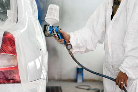 auto garage: automobile engineer spraying paint on a white car in a special garage Stock Photo