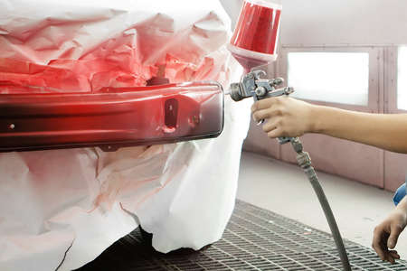 masking: professional worker spraying red paint on a car element Stock Photo
