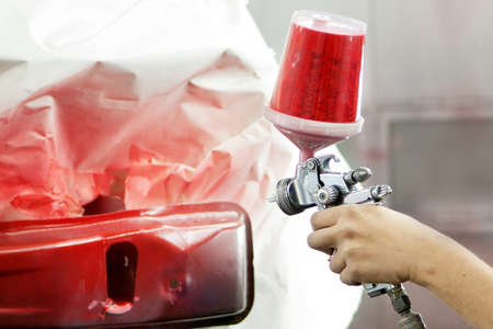 car garage: Worker using paint spray gun for painting a car