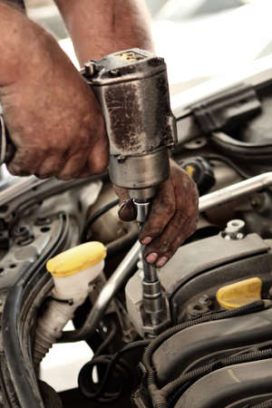 Mechanic using impact wrench for unscrewing engine components photo