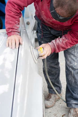 buff: Auto mechanic prepairing the car for paint job by appling polish with the power buffer machine