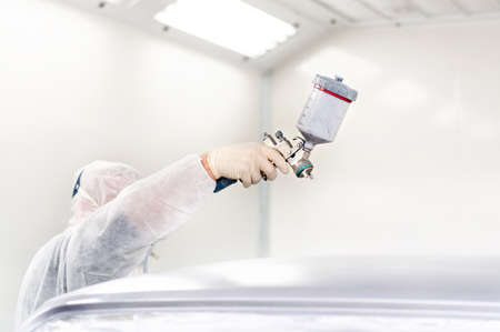 masking: Worker using a paint spray gun for painting a car in a special booth