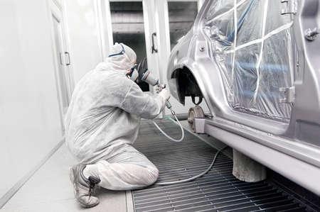 Trabalhador que pinta um carro cinza em uma garagem especial, vestindo um traje branco Banco de Imagens
