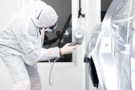 car body: Auto painter spraying paint on a car body