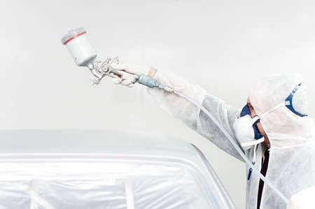 car painter working on a car in a special booth Stock Photo
