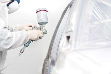 Trabalhador que pinta um carro branco em uma garagem especial
