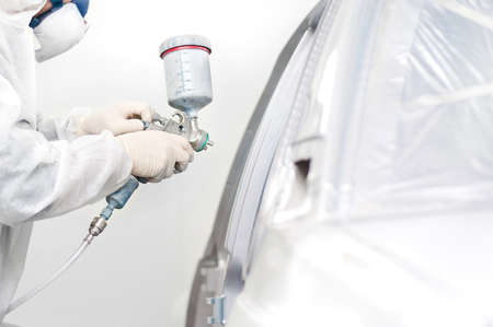 worker painting a white car in a special garage Stock Photo - 17167620