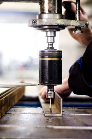 industrial engineer using a mechanical drill machine in a factory photo