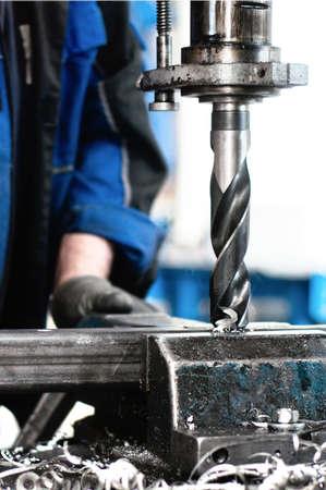 Close-up do trabalhador industrial a perfura��o de um buraco em uma barra de metal