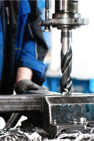 engineering tools: Close-up of industrial worker drilling a hole in a metal bar Stock Photo