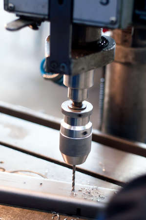 revolve: CNC industrial machine making symetrical holes into metallic bars Stock Photo