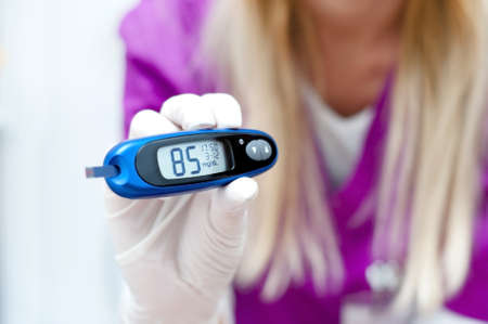 Diabetes patient measuring glucose level in blood using glucometer photo