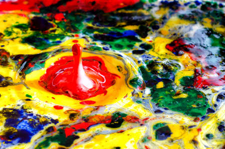 Colorful paint drops splashing in abstract paint photo