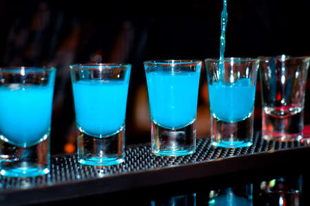 shooter drink: Bartender pours blue alcoholic drink into small glasses on bar with black background
