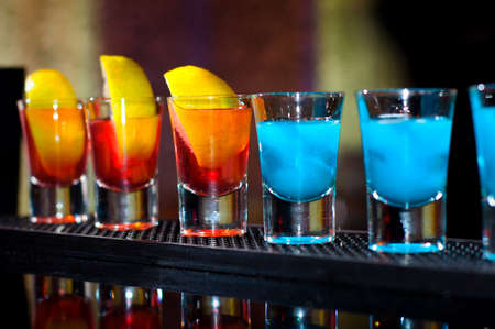 Several alcoholic shots of diferent drinks at a party in a nightclub on the counter Stock Photo