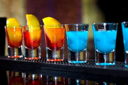 V�rios tiros de bebidas alco�licas diferent em uma festa em uma boate no balc�o Banco de Imagens