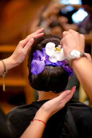 professional Hairdresser prepairing a model and fixing a flower in hair for fashion event or wedding photo