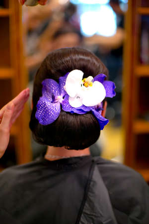 professional Hairdresser prepairing a woman model and fixing a flower in hair for fashion event or wedding photo