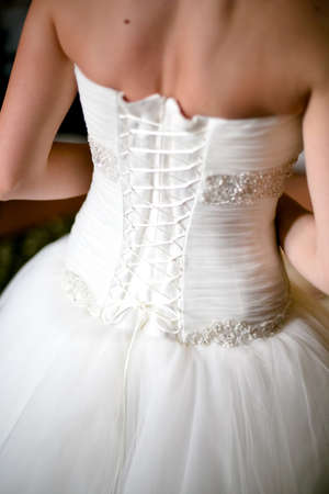 The wedding morning with close-up of gorgeos wedding dress and back of bride photo