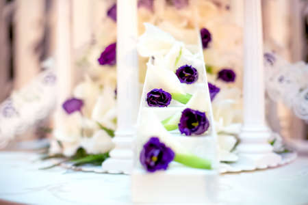 women subtle: Wedding reception with close-up of white wedding cake decoration and flowers Stock Photo