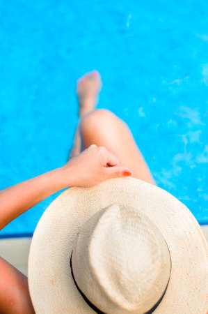 Young woman enjoying the sun at the pool while holding a hat photo