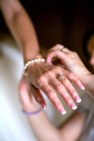 close-up of Brides sister fixing bracelet on wedding day  photo